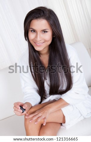 Closeup of a beautiful woman with long brunette hair sitting painting her nails