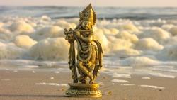 Closeup of a beautiful yellowish metal statue of Lord Krishna put on the sand beach