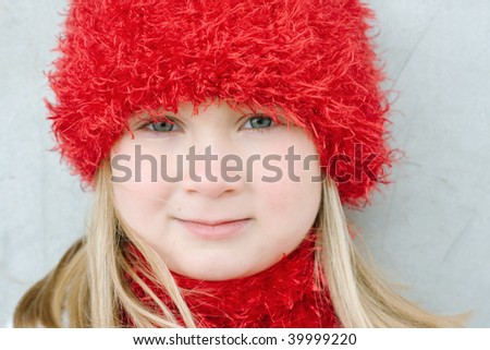 closeup of a beautiful young blond dressed in a matching red hat and scarf for winter