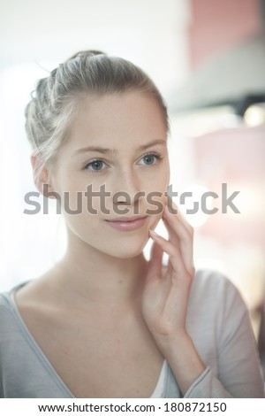 closeup of a beautiful young woman looking herself in a mirror