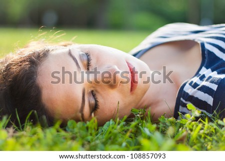 Closeup of a beautiful young woman sleeping in grass