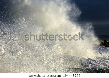 Closeup of a big stormy wave crashing against a pier of the portuguese coast (focus on the lower left foreground )