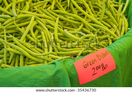 Closeup of a bin of fresh raw green beans offered for sale at a farmer\'s market.