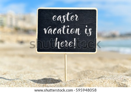 closeup of a black signboard with the text easter vacation is here written in it, on the sand of a beach #595948058