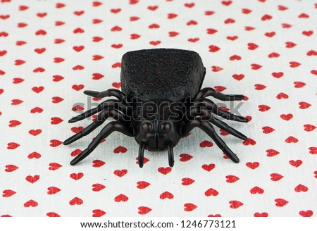 Closeup of a black toy spider on a white background with red hearts #1246773121