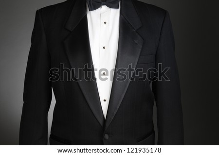 Closeup of a Black Tuxedo Jacket. Torso only on a light to dark gray background. Horizontal format.