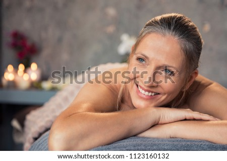 Closeup of a blonde woman in a wellness center for massage therapy. Portrait of a beautiful mature woman lying down on massage table at spa salon. Smiling senior woman awaiting beauty treatment.