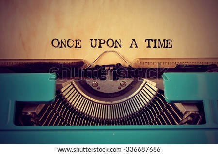 closeup of a blue retro typewriter and the text once upon a time written with it in a yellowish foil Stockfoto ©