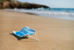 closeup of a blue used surgical mask thrown, or brought back by the ocean, on the wet sand of the seashore of a lonely beach