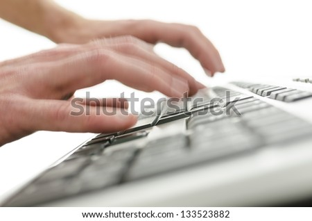 Closeup of a blurred hands typing on computer keyboard.