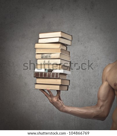 Closeup of a brawny man holding a stack of books in one hand