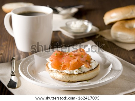 Closeup of a breakfast table with a cream cheese and smoked salmon bagel and fresh coffee.