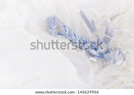 Closeup of a bridal garter with lace trim and blue satin bow against white wedding dress