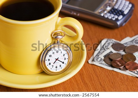 Closeup of a brightly colored yellow cup of coffee with a pocket watch on the saucer.  Cellphone in the background and dollar bills and change on the counter.