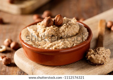 closeup of a brown earthenware bowl with natural hazelnut paste and some shelled hazelnuts on a rustic wooden table