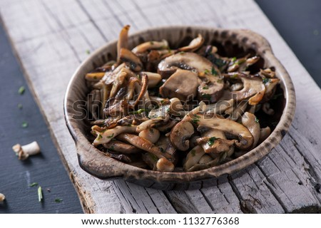 closeup of a brown earthenware bowl with some cooked mixed mushrooms, such as common mushrooms, oyster mushrooms or shiitake, on a white rustic wooden board