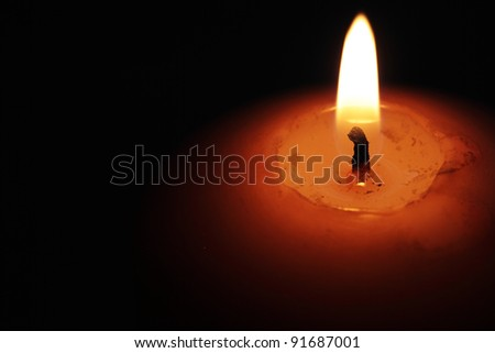 closeup of a burning candle against dark background