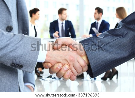 Closeup of a business handshake. Business people shaking hands, finishing up a meeting - Shutterstock ID 337196393