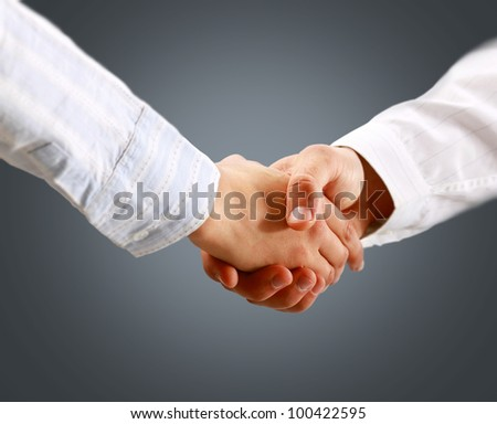 Closeup of a business handshake on grey background