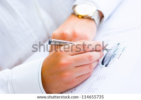 Closeup of a business man holding a pen analyzing pie chart