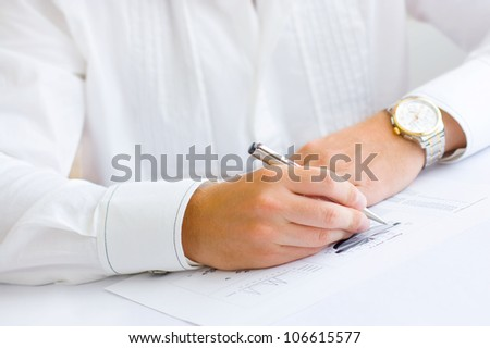 Closeup of a business man holding a pen in hand analyzing pie chart and making notes