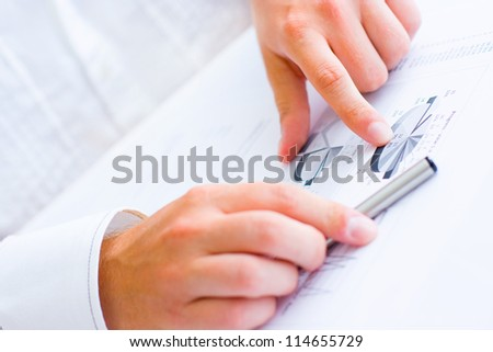 Closeup of a business man holding a pen in one hand and pointing with the other hand analyzing pie chart and making notes