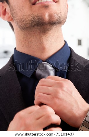 Closeup of a businessman adjusting his tie in an office environment.
