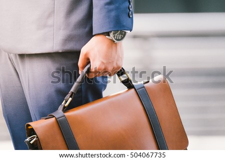 Closeup Of A Businessman Holding leather Briefcase Going To Work after rain