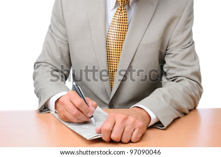 Closeup of a businessman making notes on a folded newspaper. Unrecognizable man is seated at a desk. Horizontal format over a white background. - stock photo