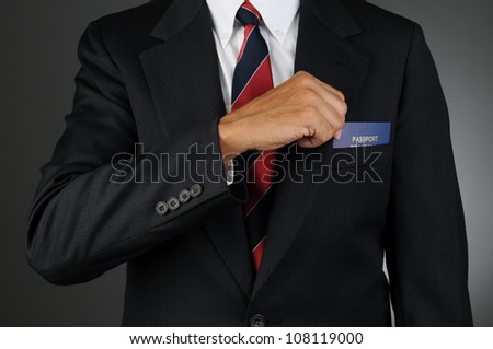 Closeup of a businessman reaching into his breast pocket to get his passport. Horizontal format over a light to dark gray background.