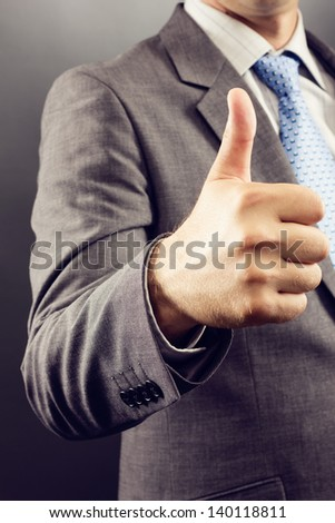 Closeup of a businessman's hand showing thumb up  isolated on gray