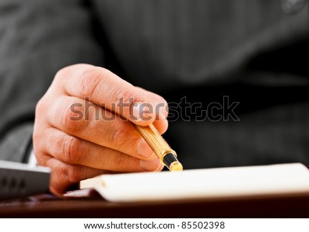 Closeup of a businessman's hands while writing some documents