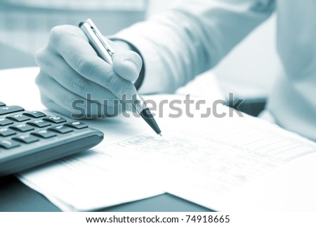 Closeup of a businessman's hands while writing some documents - blue toned image