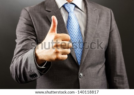 Closeup of a businessman showing thumb up  isolated on gray