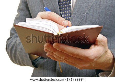 Closeup of a businessman taking notes in a small notebook. Hands and torso only. In white background.