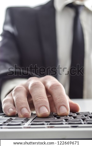 Closeup of a businessman using computer. His suit and tie in background.