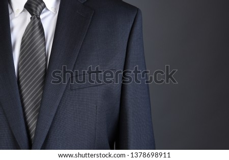 Closeup of a businessman wearing a Charcoal Gray Suit with white shirt and Striped tie. #1378698911