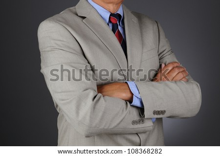 Closeup of a businessman wearing a light gray suit standing with his arms crossed. Horizontal format over a light ot dark gray background. Man is unrecognizable.