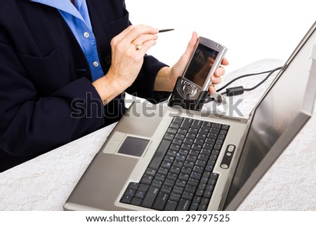 Closeup of a businesswoman transferring data from her PDA to her laptop.
