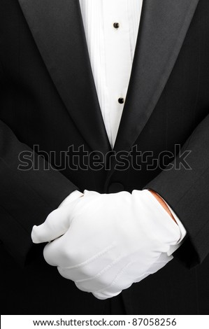 Closeup of a butler with his white gloved hands in front of his body. Man is wearing a tuxedo showing only his torso in vertical format.