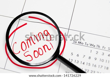 """Closeup of a calendar with """"Coming Soon"""" text in red with magnifying glass"""