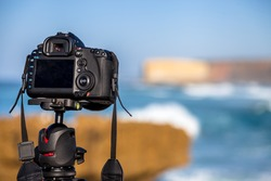Closeup of a camera on a tripod outdoors. Background Landscape out of focus. Concept of hobbies, work, travel, tourism and professional photography.