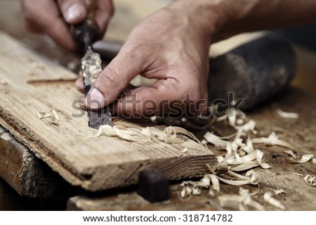 Closeup of a carpenter hands working with a chisel and carving tools on wooden workbench