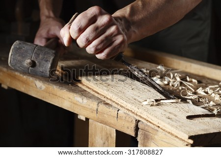Closeup of a carpenter hands working with a chisel and hammer on wooden workbench
