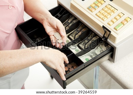 Closeup of a cashier's hands making change from a full cash register.