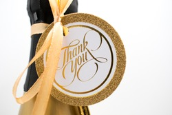 Closeup of a champagne bottle with a card saying Thank You.