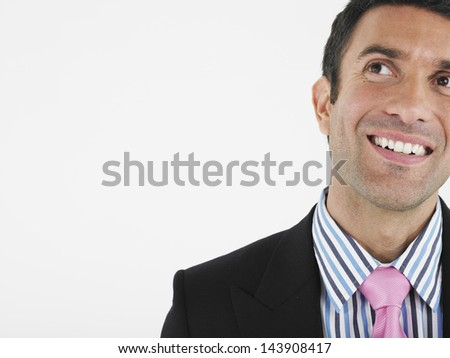 Closeup of a cheerful businessman looking up against white background