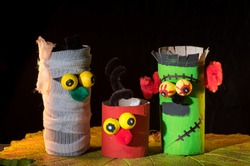 Closeup of a child's handicraft figurines made of toilet paper rolls and a clay pumpkin