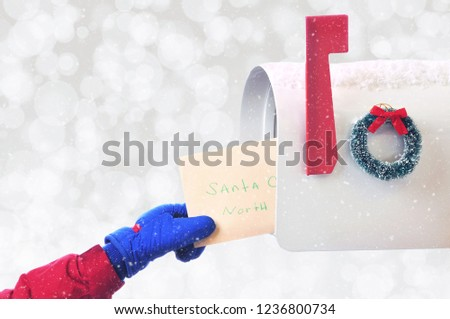 Closeup of a childs hand placing a Letter to Santa Claus in a mail box on a snowy silver bokeh background, with room for your copy.