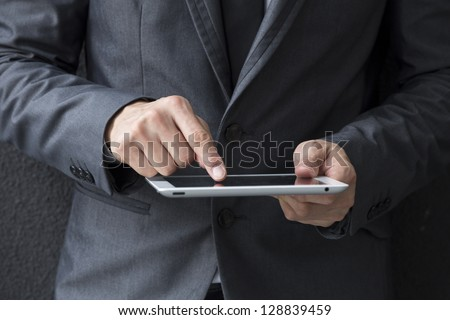 Closeup of a Chinese man with a tablet computer Asian business man using digital tablet computer leaning against a black wall